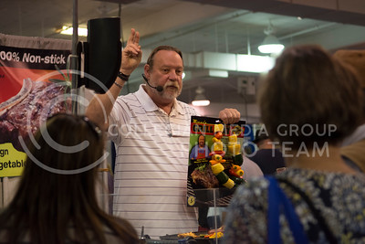 A representative of Miracle Grill Mat talks with Kansas State Fair attendees in the Farm, Industry and Auto Exhibits at the Kansas State Fair in Hutchinson, Kansas on Sept. 12, 2015. (Cassandra Nguyen | The Collegian)