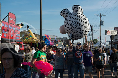 Jarrod Darks, from Oakley, Kansas, hold his giant stuffed cow up high while walking around the fairgrounds at the Kansas State Fair in Hutchinson. Darks won the stuffed animal after successfuly getting a ring around a bottle. (Photo by Evert Nelson | The Collegian)
