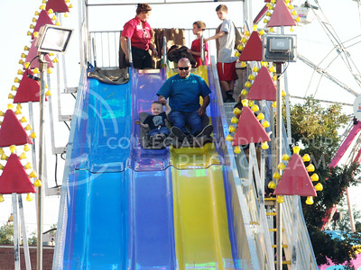 Robert Raigoza holds Paxton Raigoza's hand as they conquer the slide at the Kansas state fair Sept. 12, 2015. (Jessica Robbins | The Collegian)