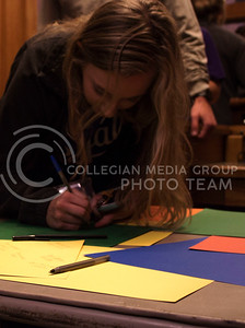 Hannah Willems, a sophomore in athletic training, writes on a card for Kaiden Schroder at the FarmHouse Fraternity philanthropy event, Kakes for Kaiden, on Oct. 27, 2015. (Regan Tokos | The Collegian)