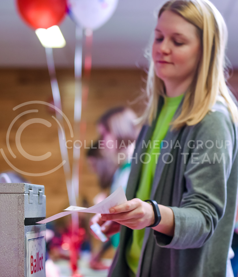 Julia Hilts, senior in chemical engineering, drops her ballot in the ballot box at the Riley County Republican Party Presidential Caucus Mar. 5, 2016, at Manhattan High School. (Parker Robb   The Collegian)