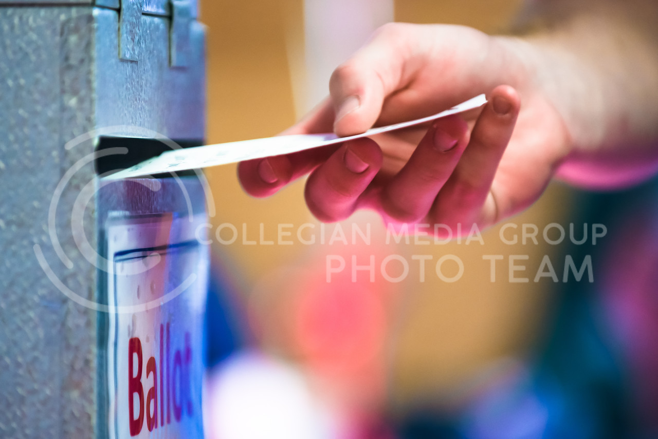 A voter drops his ballot into the ballot box at the Riley County Republican Party Presidential Caucus Mar. 5, 2016, at Manhattan High School. (Parker Robb | The Collegian)