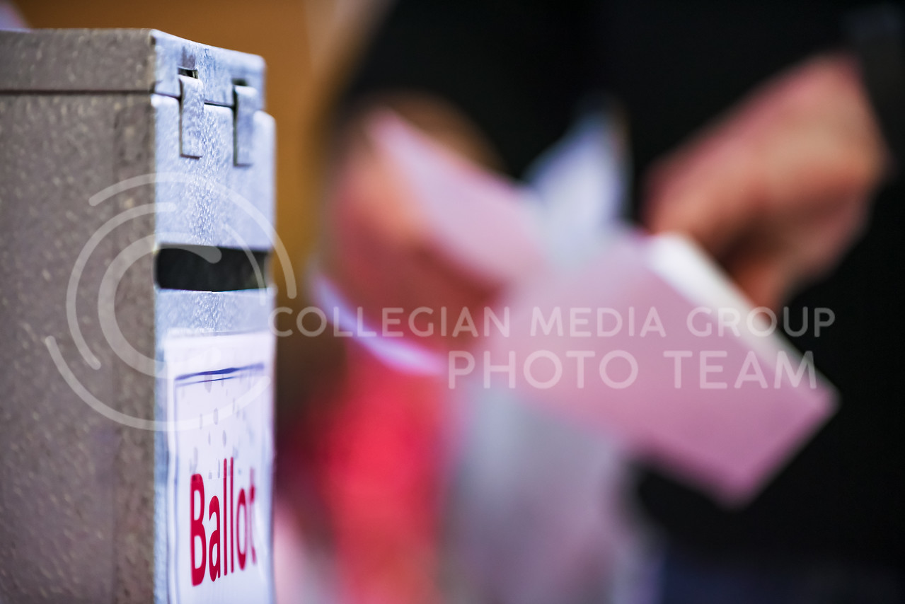 A voter stuffs his ballot into an envelope before dropping it in the ballot box at the Riley County Republican Party Presidential Caucus Mar. 5, 2016, at Manhattan High School. (Parker Robb   The Collegian)