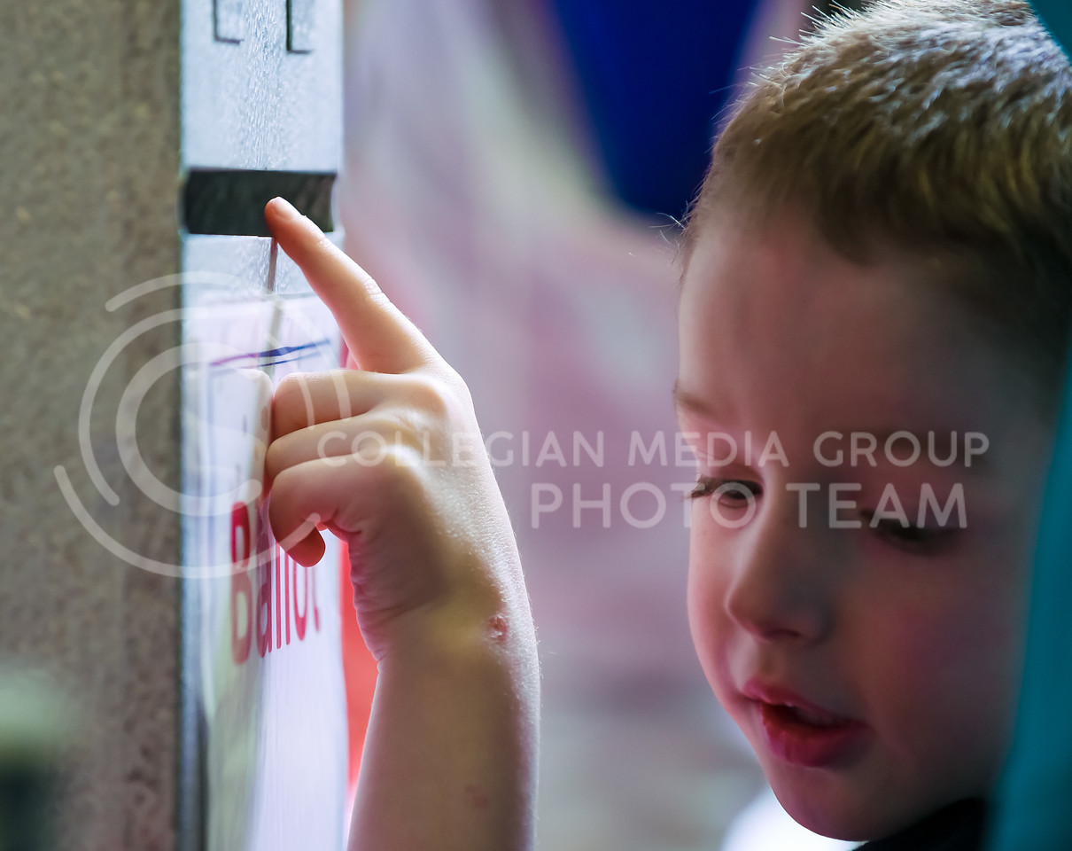 A boy looks into the abyss of the ballot box at the Riley County Republican Party Presidential Caucus Mar. 5, 2016, at Manhattan High School. (Parker Robb   The Collegian)