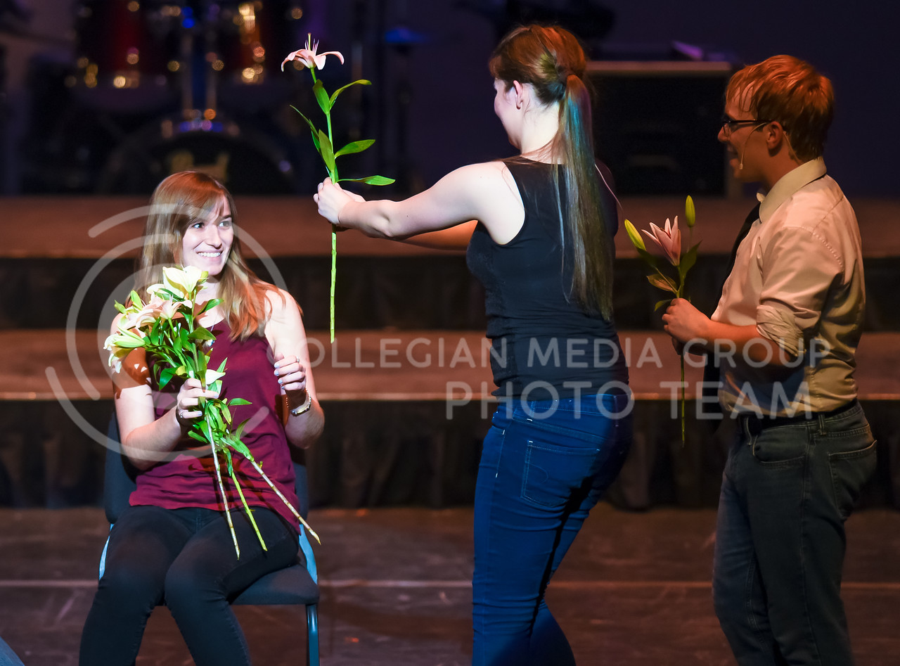 The K-State Singers line up to hand flowers to Ali Dawes, '15 graduate in communication sciences and disorders, before Singer Mark Hay, senior in theater, proposes to girlfriend Ali Dawes on stage during the Singers' portion of their joint concert with In-A-Chord Apr. 22, 2016, in McCain Auditorium. (Parker Robb | The Collegian)