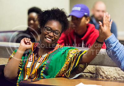 Ebony Paul, senior in apparel and textiles and marketing, high fives Casha Mills, junior in English, after watching an inspirational video presented by other Black Student Union members. (Cassandra Nguyen | The Collegian)