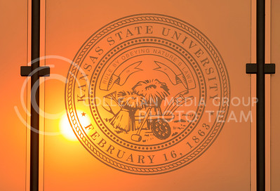 The sun shines through the K-State seal on the Student Union skywalk window as the sun sets on March 3, 2016. (George Walker | The Collegian)