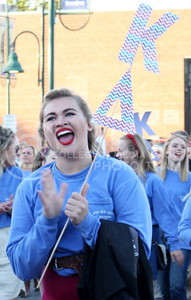 Elissa Bergmeier, freshmen in political science, cheers in the K-State Homecoming Parade through Aggievile with her Kappa Delta sorority sisters and their homecoming partners Phi Gamma Delta and Alpha Kappa Lambda on Oct. 16, 2015. (Miranda Snyder | The Collegian)