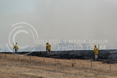 A couple of Konza Prairie Biological Research Center volunteers walk around the end of smouldering wild grass on March 9, 2016. (Photo by Evert Nelson)