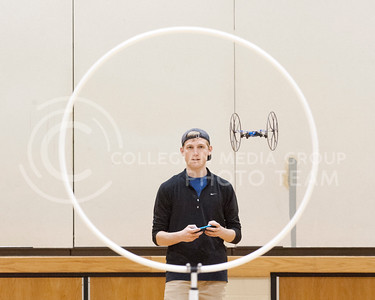Nicholas Patterson, senior in mass communcations, flies a Parrott 'Rolling Spider' drone through a hoop in the gym of Eisenhower Middle School on Tuesday March 29, 2016. Patterson is enrolled in MC 589 - Issues in Mass Communications, where they study drone, or Unmanned Aeriel System (UAS), use in journalism. On Tuesday the class was held in Eisenhower where they were able to fly under the instructor of Duke Harmon, technology coordinator for USD 383 STEM. (Photo by Evert Nelson | The Collegian)
