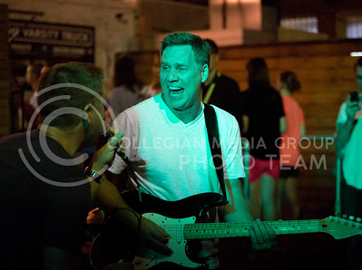 Kevin Peirce, owner of Bluestem Bistro and guitar player for Suspicious Package sings along with Todd Spreer at the The Varsity Truck during Live Music In The Alley on Aug. 28, 2015. (Emily Starkey | The Collegian)