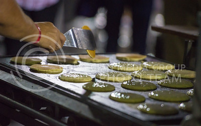 Dennis McBride, with Chris Cakes, flips pancakes during the Week of Welcome pancake feed at Memorial Stadium on Aug. 29, 2015. (George Walker | The Collegian)