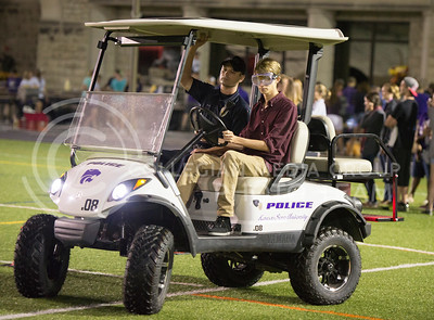 Heath Helmick, freshman in mechanical engineering, drives a golf cart while wearing drunk googles with KSU police office Michael Boller during the Week of Welcome pancake feed at Memorial Stadium on Aug. 29, 2015. The golf cart was paid for with a grant from the Kansas Department of Transportation for an educational program. (George Walker | The Collegian)