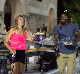 Anna Proffitt, junior in kinesiology, catches a pancake while D.J. Johnson, senior in entrepreneurship, watches during the Week of Welcome pancake feed at Memorial Stadium on Aug. 29, 2015. (George Walker | The Collegian)