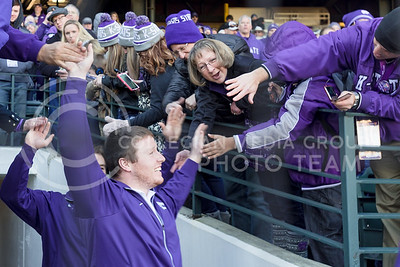 K-State fans greet the K-State football players with high-fives as the players enter the field at the K-State Alumni Center Liberty Bowl Pep Rally in AutoZone Park in Memphis, Tennesse, January 1, 2016. (Parker Robb | The Collegian)