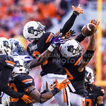 Oklahoma State defenders lunge for a long pass thrown by K-State quarterback Joe Hubener in an attempt to score a last-minute touchdown as the last seconds slipped away in the Wildcats' hear ...