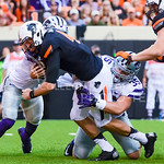 Junior linebacker Will Davis (35) and sophomore linebacker Elijah Lee (behind) bring down Oklahoma State quarterback J.W. Walsh just short of the goal line in the third quarter of the Wildca ...