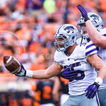 Junior linebacker Will Davis (35) comes out of a pileup holding the ball after intercepting an Oklahoma State pass as senior defensive tackle Travis Britz celebrates with him in the fourth q ...