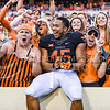 Oklahoma State linebacker Chad Whitener jumps into the stands with rambunctious fans following the Cowboys' clutch last-minute win over K-State Oct. 3, 2015, in Boone Pickens Stadium in Stillwater, Oklahoma. (Parker Robb | The Collegian)