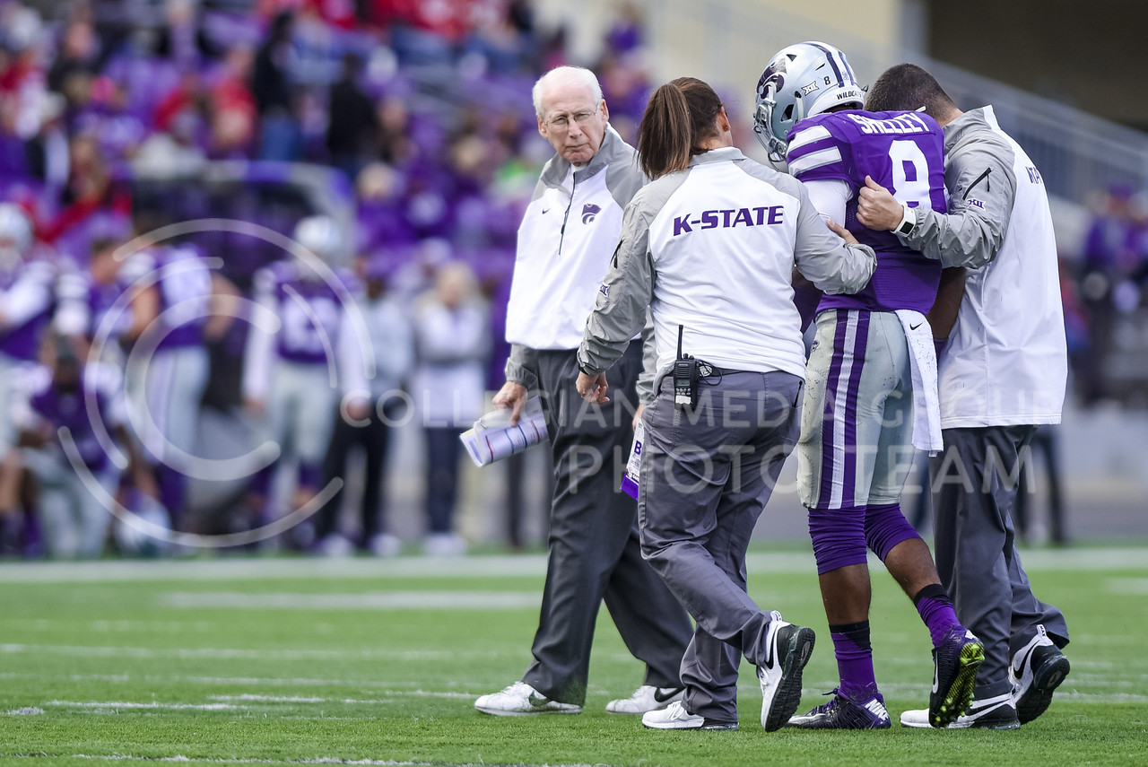 Head coach Bill Snyder and K-State football staff walk freshman defensive back Duke Shelley off the field after he is hurt in the fourth quarter of the Wildcats' 55-0 shutout loss to the No. 19 Oklahoma Sooners Oct. 17, 2015, in Bill Snyder Family Stadium. (Parker Robb | The Collegian)