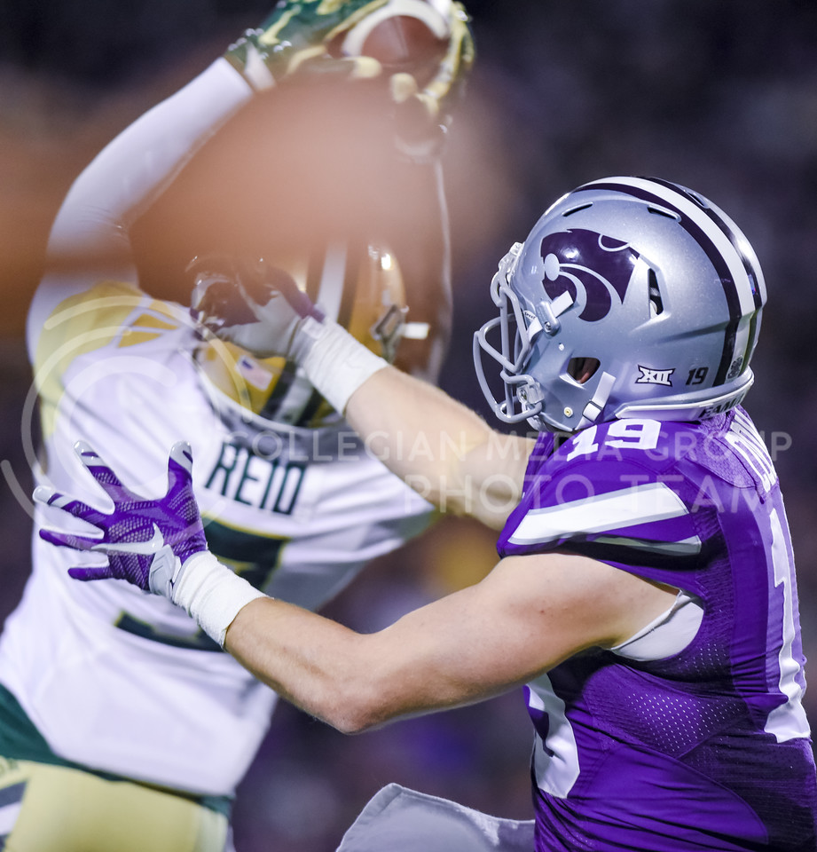 Senior wide receiver Kody Cook can only watch helplessly as Baylor defensive back Ryan Reid snatches a pass intended for him from Joe Hubener out of the air as K-State tries to close the gap in Baylor's 14-7 lead in the second quarter of the Wildcats' 24-31 loss to the No. 2 Bears Nov. 5, 2015, in Bill Snyder Family Stadium. The 'Cats came close to defeating the Bears, but fell just short due to three costly turnovers. Baylor scored a touchdown on an 81-yard pass the very next play. (Parker Robb | The Collegian)