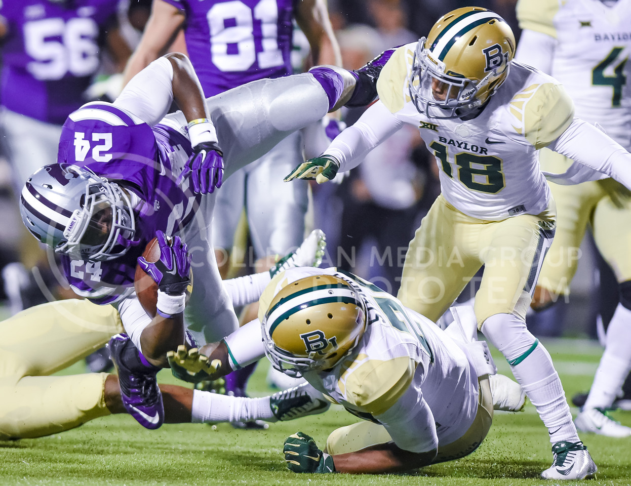 Junior runningback Charles Jones goes flying as he is stopped at the one yard line by a host of Baylor defenders after a 13 yard run on K-State's first possession of the first quarter of the Wildcats' 24-31 loss to the No. 2 Bears Nov. 5, 2015, in Bill Snyder Family Stadium. (Parker Robb | The Collegian)