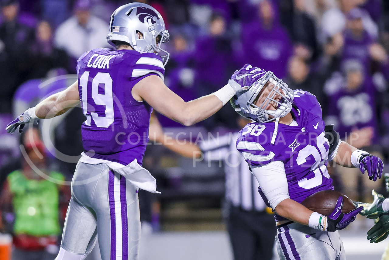Senior wide receiver Kody Cook (19) slaps the helmet of redshirt freshman fullback Winston Dimel (38) in congratulations after Dimel caught a pass and ran for 46 yards as K-State, down 31-17, attempts a comeback in the final eight minutes of the fourth quarter of the Wildcats' 24-31 loss to the No. 2 Bears Nov. 5, 2015, in Bill Snyder Family Stadium. (Parker Robb | The Collegian)