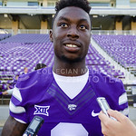 Junior wide receiver Deante Burton answers questions from reporters with a grin on his face at K-State Football's media day August 8, 2015. (Parker Robb | The Collegian)