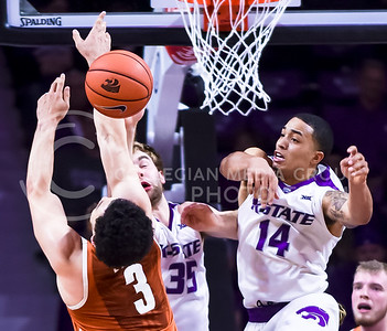 Senior forward Justin Edwards defiantly knocks a shot out of the hands of Texas guard Javan Felix in the first half of the Wildcats' 71-70 loss to the No. 25 Longhorns Feb. 22, 2016, in Bramlage Coliseum. Edwards led the 'Cats with 20 points, 8 rebounds, 5 assists, and 2 blocks, however K-State barely came up short in the final seconds to another top 25 team and lost their fourth consecutive game to the Longhorns--the longest losing streak in series history. (Parker Robb | The Collegian)