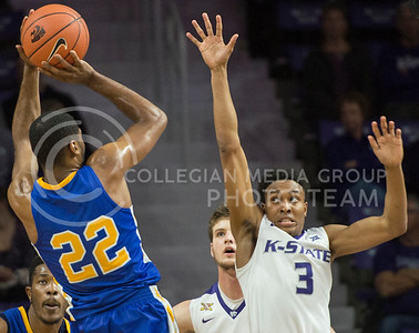 Freshman guard Kamau Stokes reaches to block Coppin State junior guard Keith Shivers on Dec. 9, 2015 at Bramlage Coliseum.  Stokes had five assists in the game against Coppin State.  (Rodney Dimick | The Collegian)