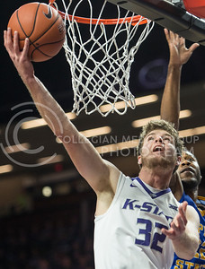Freshman forward Dean Wade reaches around the basket to score on Dec. 9, 2015 at Bramlage Coliseum.  Wade took in a total of 12 points against Coppin State.  (Rodney Dimick | The Collegian)