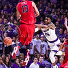 Junior forward Wesley Iwundu (25) shovels a pass around Ole Miss forward Anthony Perez (13) in the second half of the Wildcats' 69-64 win over the Rebels in the teams' Big 12-SEC Challenge game Jan. 30, 2016, in Bramlage Coliseum. (Parker Robb | The Collegian)