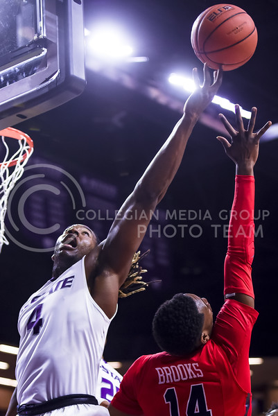 Senior forward D.J. Johnson (4) gets a finger on the rebound over Ole Miss guard Rasheed Brooks in the second half of the Wildcats' 69-64 win over the Rebels in the teams' Big 12-SEC Challenge game Jan. 30, 2016, in Bramlage Coliseum. (Parker Robb | The Collegian)