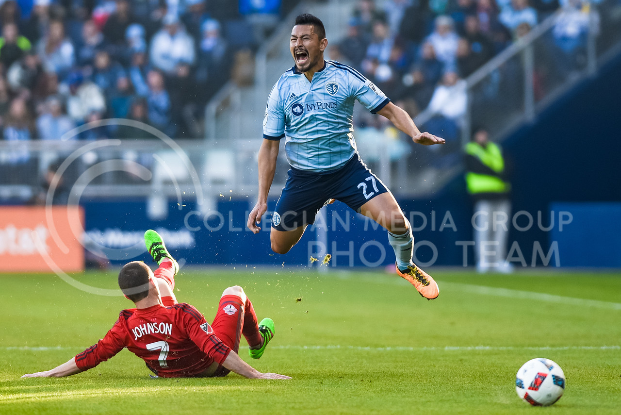 Sporting KC midfielder Roger Espinoza shouts in midair as Toronto FC midfielder Will Johnson fouls him by sweeping out his legs in the first half of Sporting's 1-0 victory over Toronto Mar. 20, 2016, at Children's Mercy Park in Kansas City, Kansas. (Parker Robb   The Collegian)