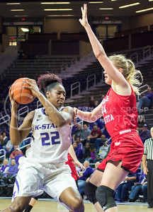 Junior center Breanna Lewis attempts to dribble around South Dakota junior forward Abigail Fogg at the women's basketball game against South Dakota University on Nov. 19, 2015 in Bramlage Coliseum. (Cassandra Nguyen | The Collegian)
