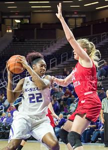 Junior center Breanna Lewis attempts to dribble around South Dakota junior forward Abigail Fogg at the women's basketball game against South Dakota University on Nov. 19, 2015 in Bramlage Coliseum. (Cassandra Nguyen | The Collegian)