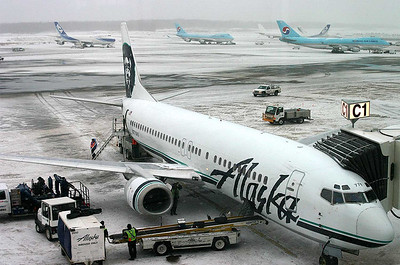 Transient 747's wait for various services while this Alaska 737-400 prepares for boarding.