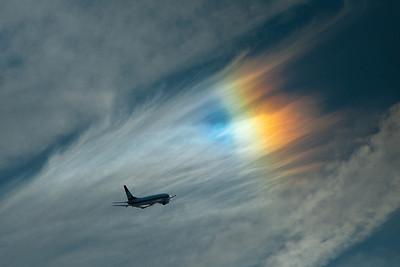 The sun rainbows the thin, high clouds while LOT Airlines 737 departs Heathrow. Heathrow 2009.