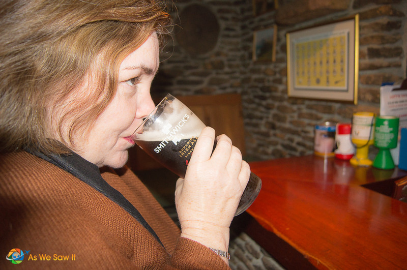 Linda enjoys a pint of Smithwick's ale at a pub counter