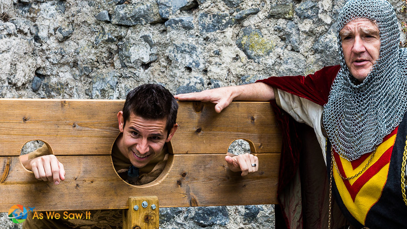 Sir Mike stands next to a tour guest whose head and hands are in a pillory