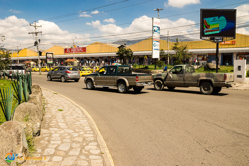 cars pass in front of El Arenal, Cuenca's local market