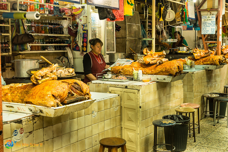 Woman behind a counter on a row of stalls selling cooked pigs.
