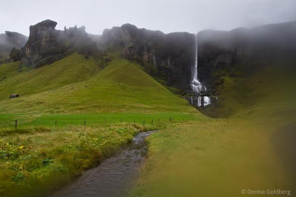 waterfall on a hillside engulfed in fog