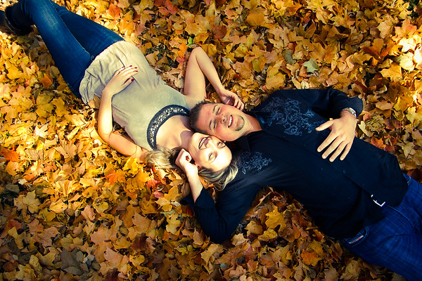 Couple laying in Fall leaves at engagement photography session in Joliet Rockford Chicago wedding engagement photographer