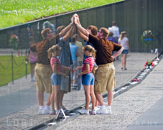 A family makes a pencil rubbing of a name on The Memorial Wall at the Vietnam Veterans Memorial in Washington, DC. The visitors' reflection in the polished black granite is meant to symbolically bring the past and the present together.