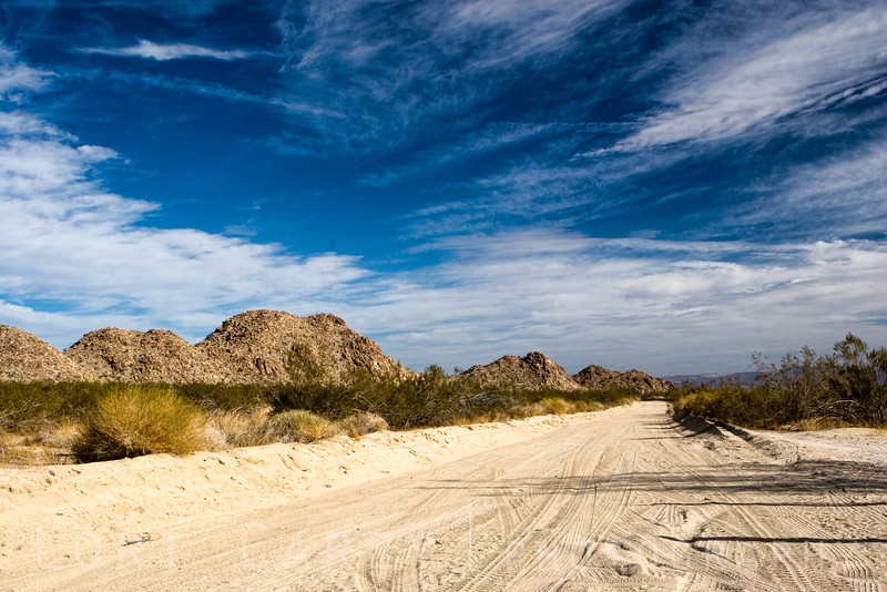The scenic Black Eagle Mine Road in Joshua Tree National Park wuns along the edge of the Pinto Basin and winds through canyons in the Eagle Mountains, passing near several old mining sites.