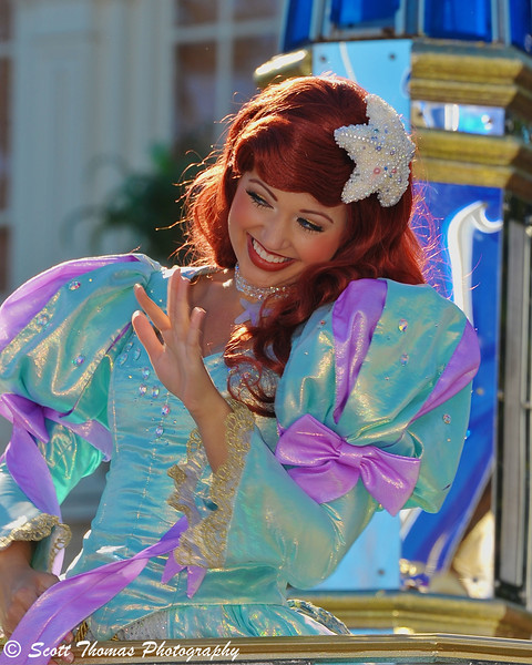 Princess Ariel waving to her admirers during a parade on Main Street USA in the Magic Kingdom.