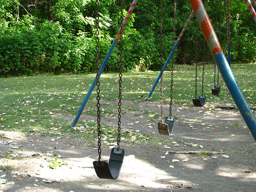 An empty set of swings in a park devoid of life and movement (20080727_10218)