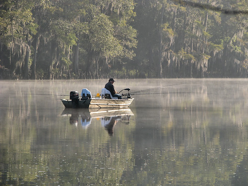 A man sitting in early morning fog fishing from his boat in the middle of Big Cypress Bayou (20081011_13535)