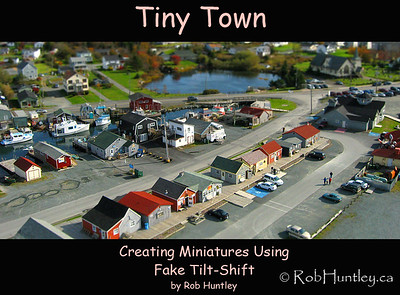 Fisherman's Cove in Dartmouth, Nova Scotia. The low level aerial photograph of the line of shops is ideally suited for a Fake Tilt-Shift Miniature. The houses take on the appearance of Parker Bros. Monopoly figures and even the people look artificial. The background has been thrown out of focus plus the colour saturation has been greatly boosted to give the objects a plastic-like, toy-like appearance.